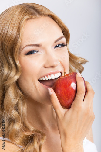 Woman eating apple, on grey