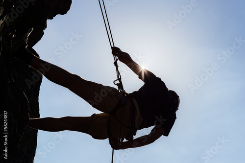 Silhouetted Man Climbing Rock