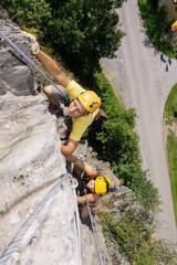 Man And Woman Climbing Rock