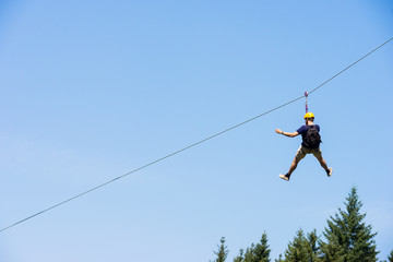 Young Man Riding On Zip Line