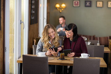 Female Friends Using Digital Tablets At Table
