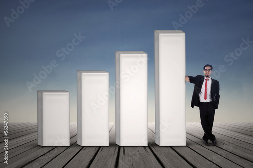 Asian businessman in black suit standing next to bar chart