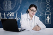 Beautiful female doctor writing prescription on blue digital