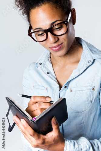Young black woman taking notes at home