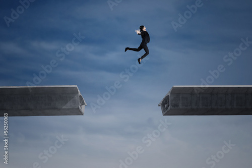 Young businesswoman jumping over a gap in the bridge