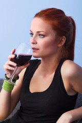 Portrait of young woman with glass red wine
