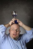 Man with winning trophy over his head