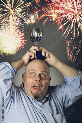 Man with winning trophy  and fireworks in backgroun