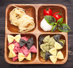 Italian pasta, farfalle, basil and tomatoes in a wooden box