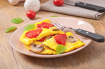 Delicious omelet with tomatoes and mushrooms for breakfast