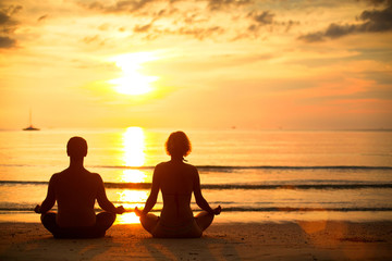 Young couple practicing yoga on the beach at sunset.
