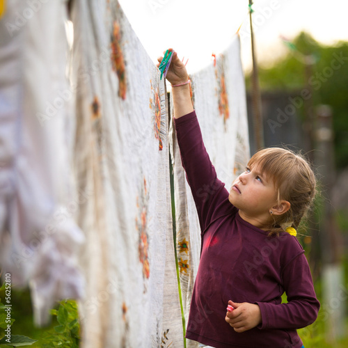 Lovely little five-year girl with clothespin outdoor