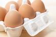 木のテーブルの上に容器にはいった生卵
