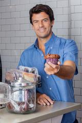 Mid Adult Man Holding Cupcake At Supermarket