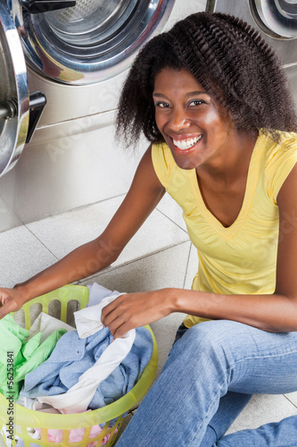 Woman With Basket Of Clothes Sitting In Laundry