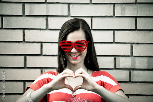 Young woman make heart with fingers