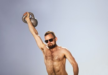 Male athlete performing one-handed kettle bell swings