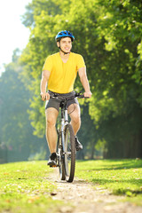 Full length portrait of a young man biking in a park