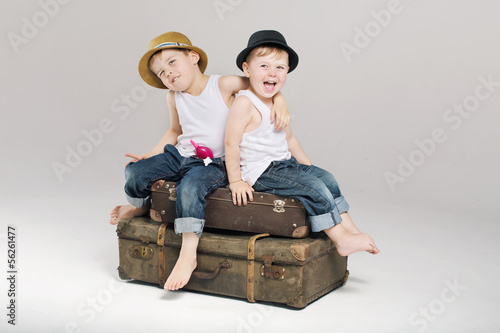 Two small brothers sitting on the suitcases
