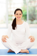pregnant woman sitting on mat