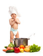 Little boy in chef's hat standing among fresh vegetables