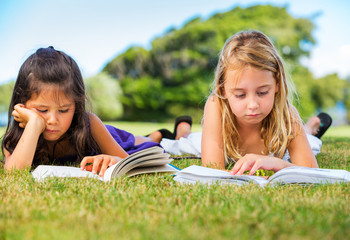 Little Girls Reading Books on Grass