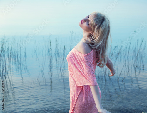 Sensual blonde girl enjoying cold lake water