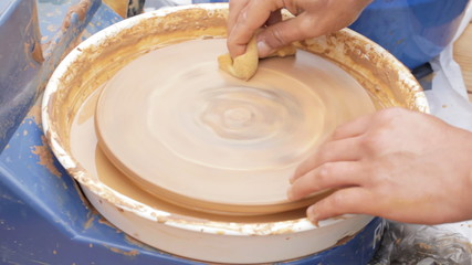 Clay shaping on potter's wheel.