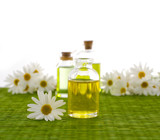 Glass Bottle with daisy flowers, massage oil on green mat