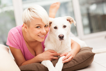 Blonde woman is playing with her dog