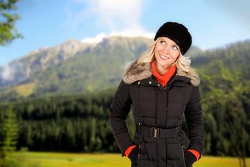 Lachende junge Frau vor Berghintergrund