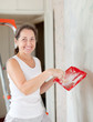 woman paints wall with brush at home