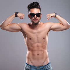 topless man flexes his biceps