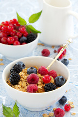 breakfast - muesli with berries, milk, selective focus.