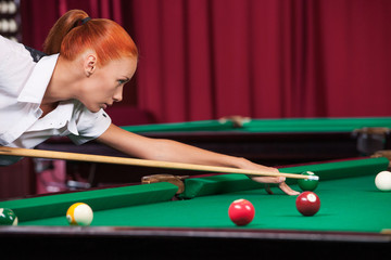 Woman playing pool. Side view of confident young woman aiming th