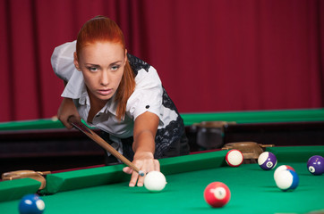Woman playing pool. Confident young woman aiming the billiard ba