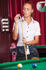 Pool player. Confident young woman holding pool cue