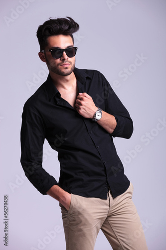 young fashion man with a hand on his collar