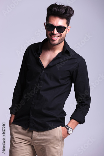 young fashion man smiles with hand in pocket