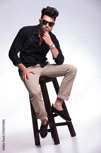 seated young man looks pensive