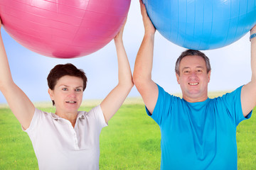 Man and woman holding up exercise ball