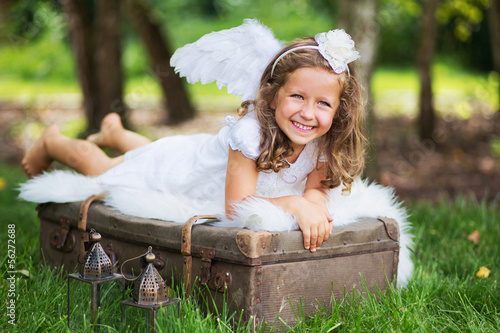 Small cute angel resting on the suitcase