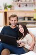 junges lächelndes paar sitzt mit laptop auf dem sofa