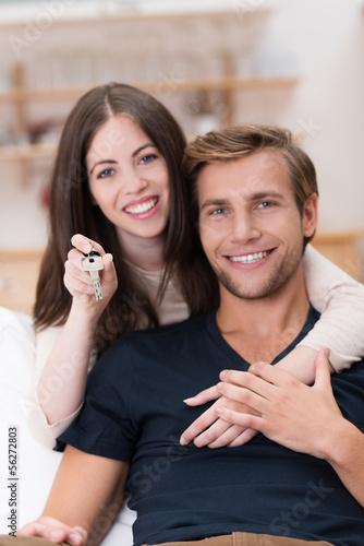 glückliches paar zeigt schlüssel der eigenen wohnung