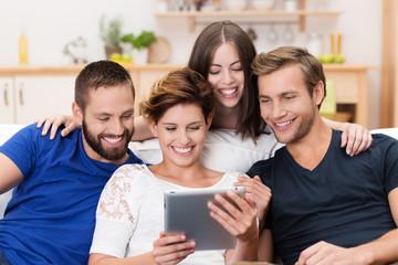 lachende freunde schauen zusammen auf tablet-pc