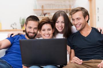 freunde schauen lachend auf laptop