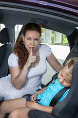 Mother showing shh gesture when daughter asleep in car seat
