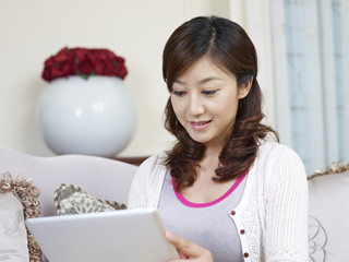 young asian woman using tablet computer at home