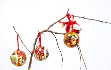 Three Red Christmas Decorations On A Dry Branch