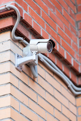 Video surveillance camera on brick wall